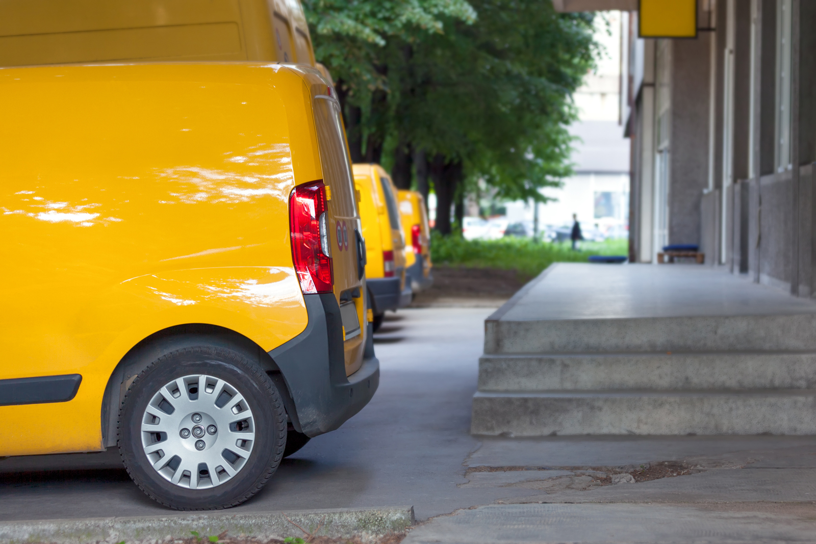 Three yellow vans parked next to each other in-front of a depot ready for deliveries