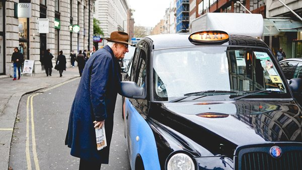 An elderly man speaking to a taxi driver to ask for a lift