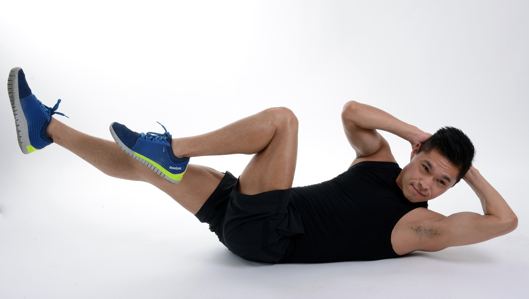 A man in gym clothing exercising his abs