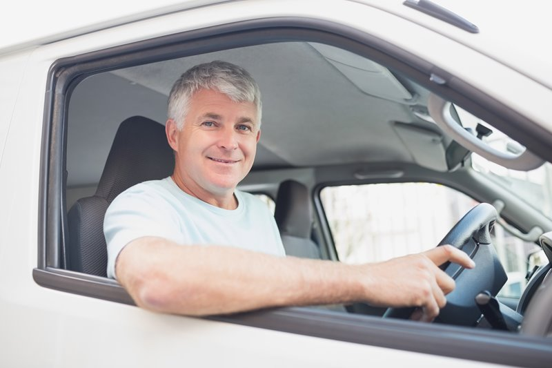 Man driving silver van with smile on his face
