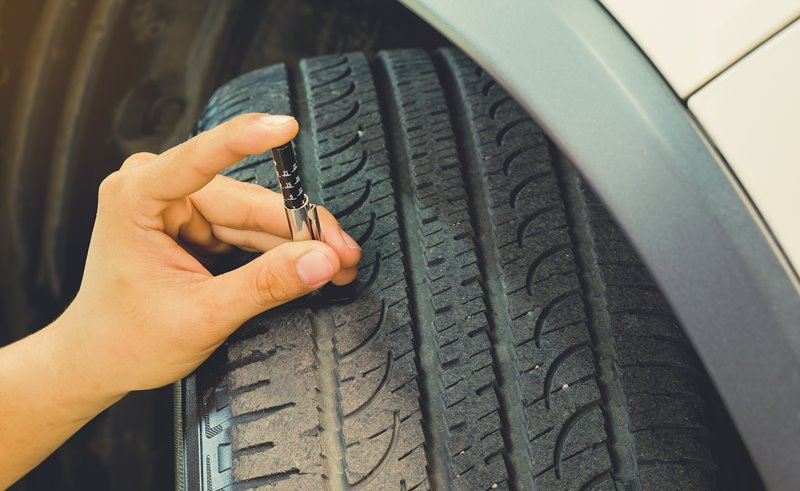 Driver checking tyre tread depth using tool