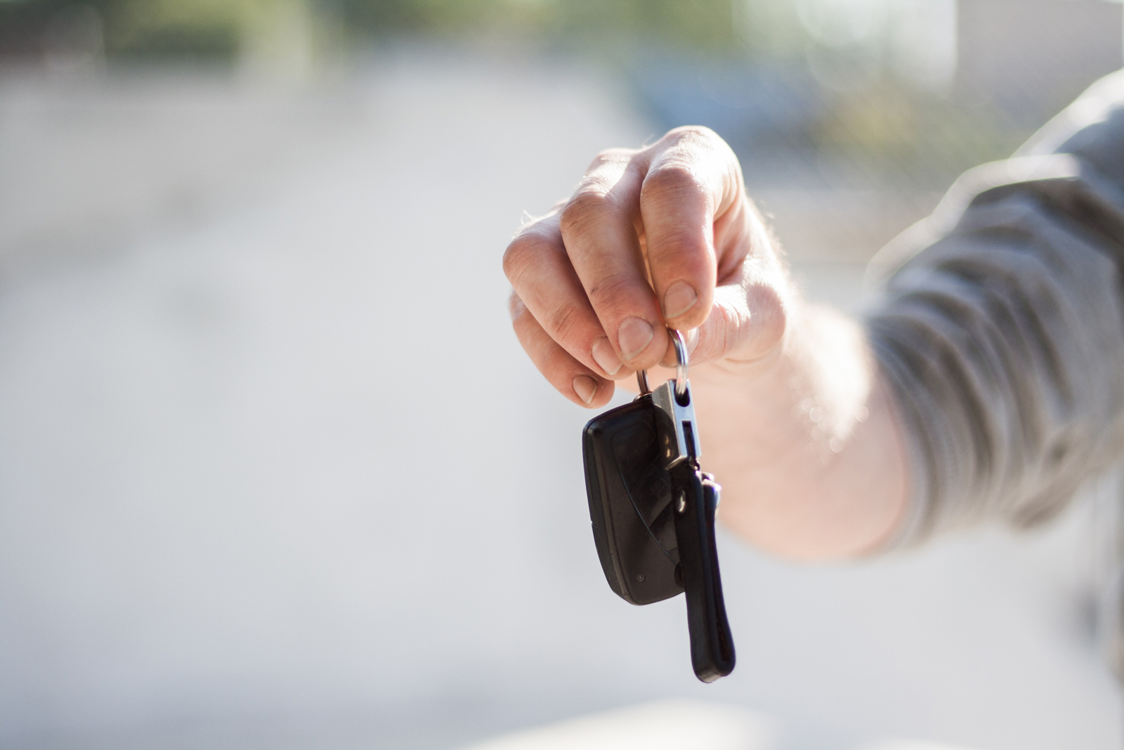 A person handing keys to a new driver