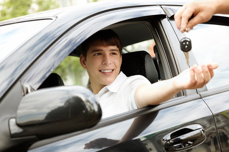A young driver sitting in a car being passed the keys