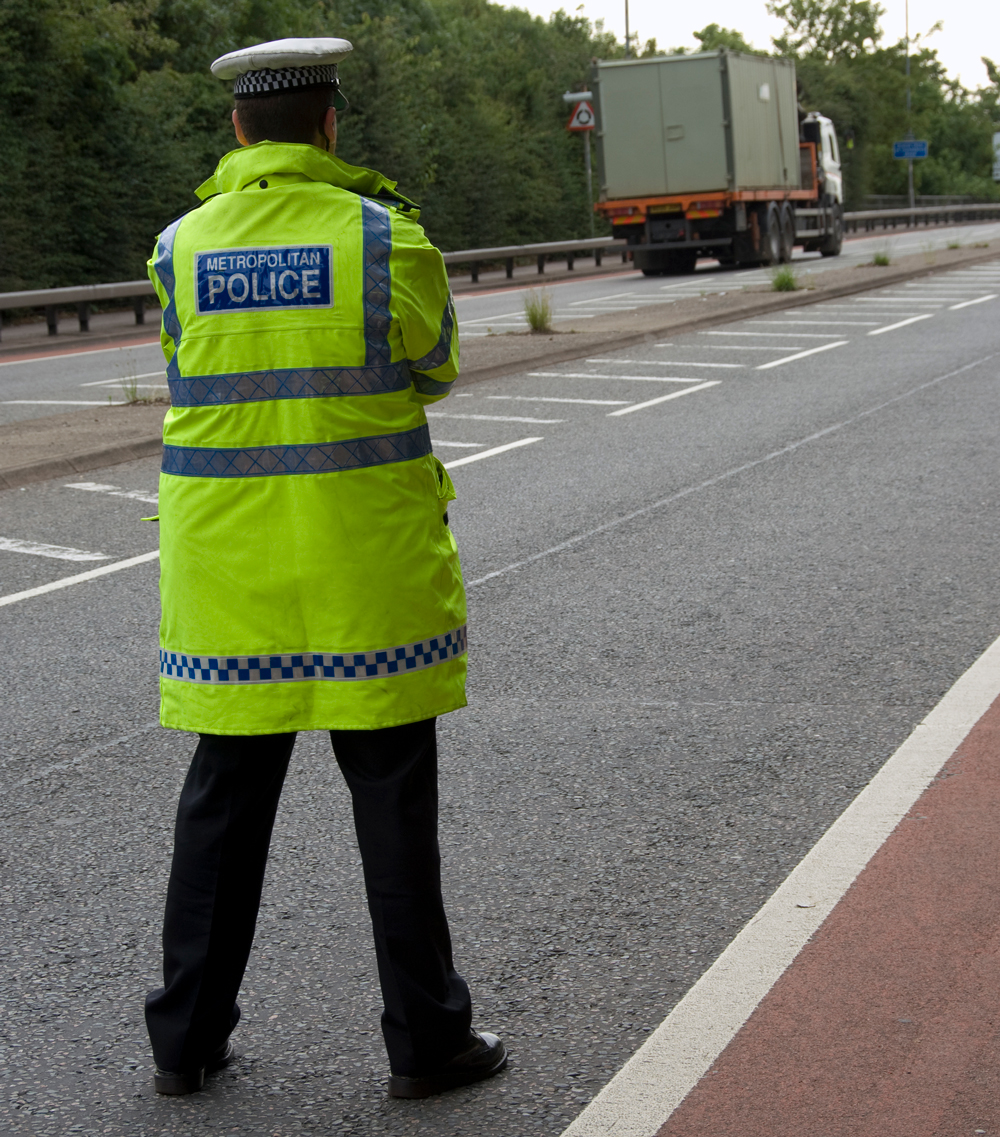 A police officer standing at a raodside watching traffic