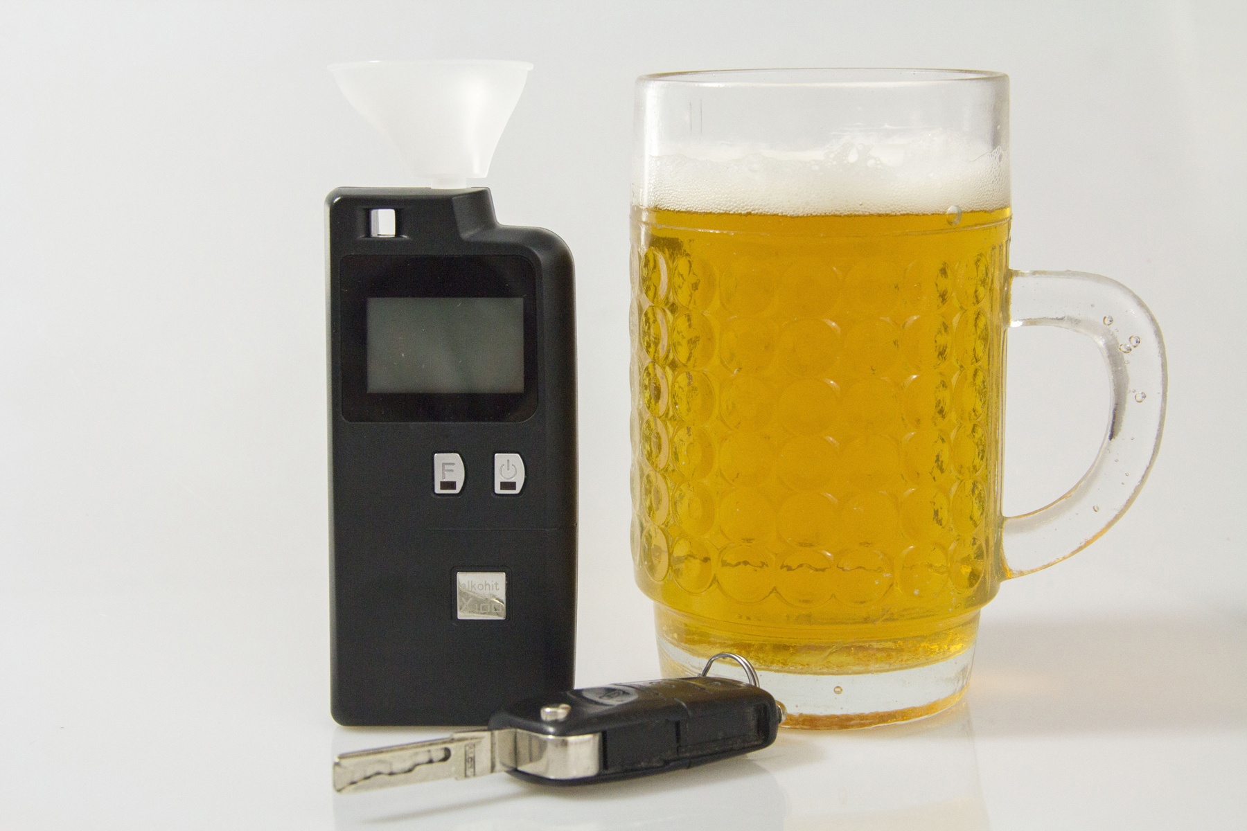 An electronic breathalyser on a table next to a pair of car keys and a pint of beer