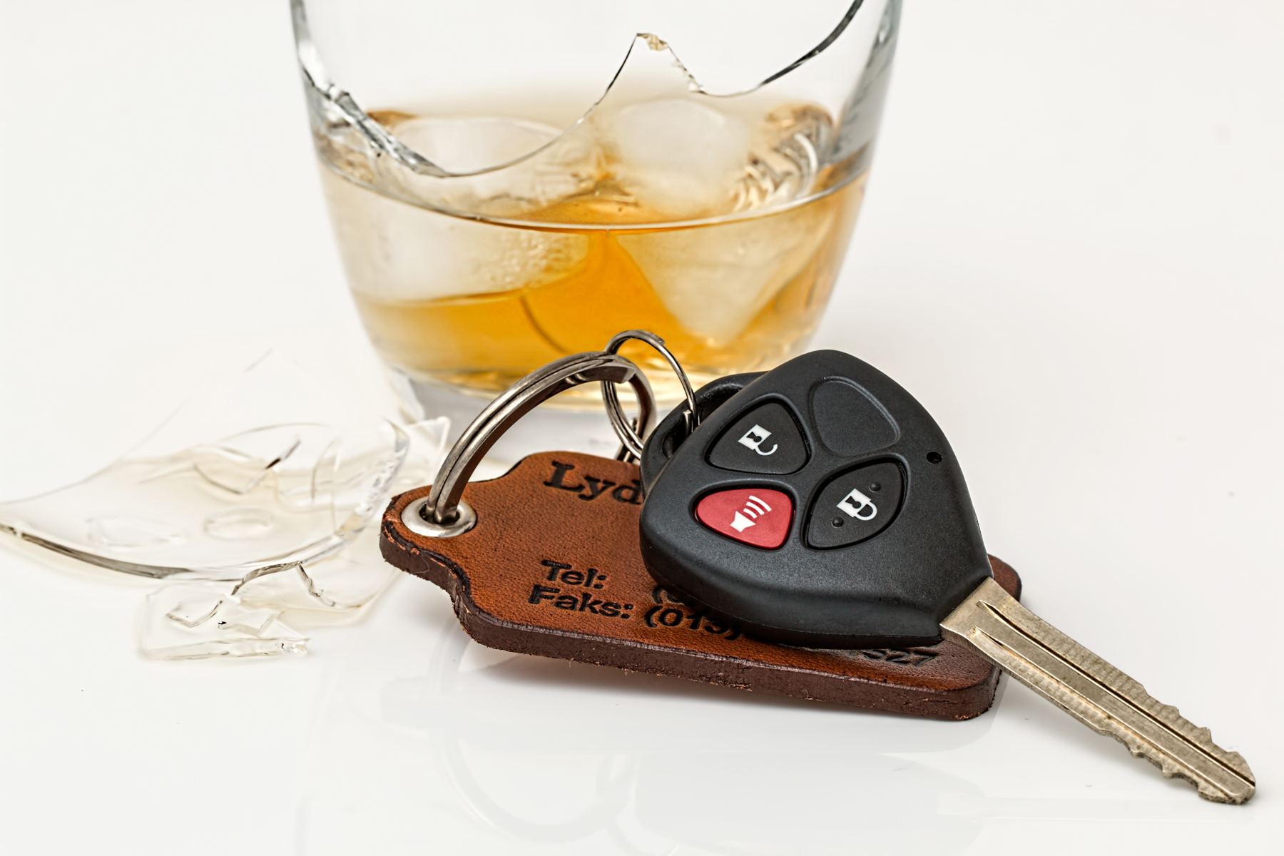 A glass of alcohol next to a pair of car keys