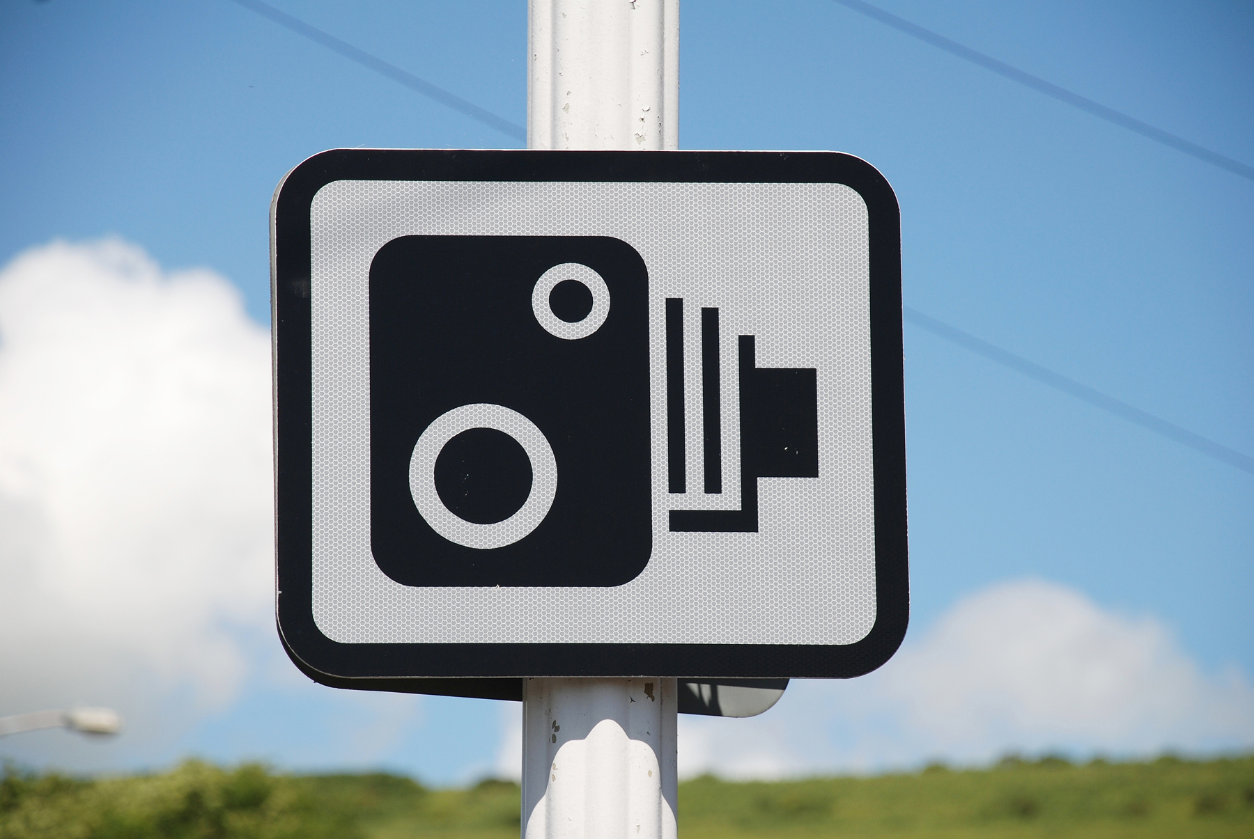 A sign next to a road depicting a speed camera