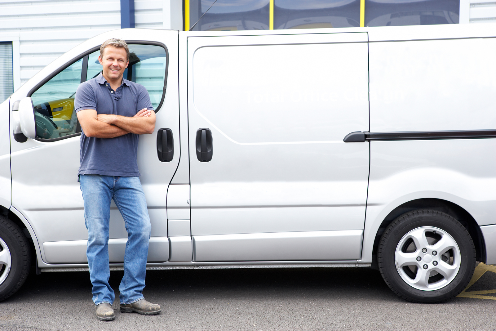 A courier leaning against the side of his silver van