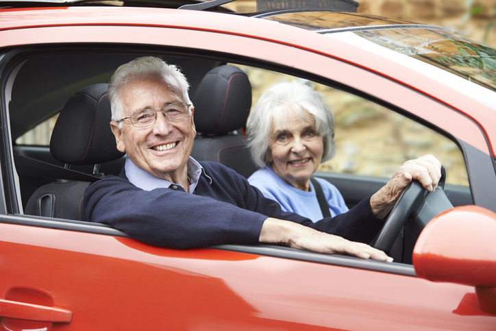 An elderly man and his wife smiling as they drive