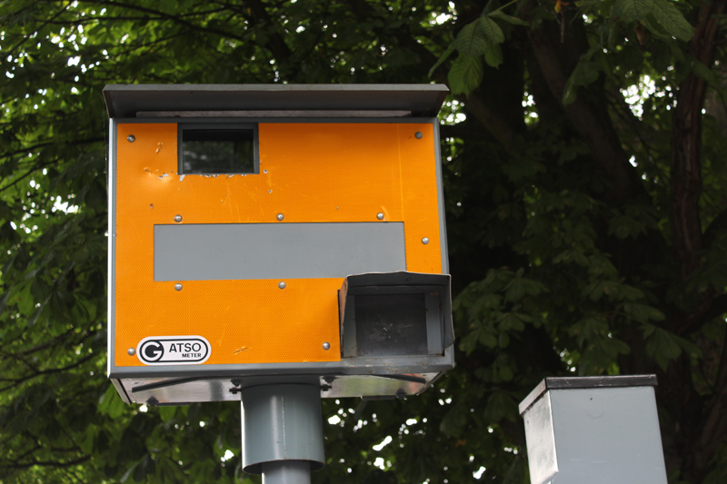 A yellow speed camera at a roadside with green leafy trees behind it