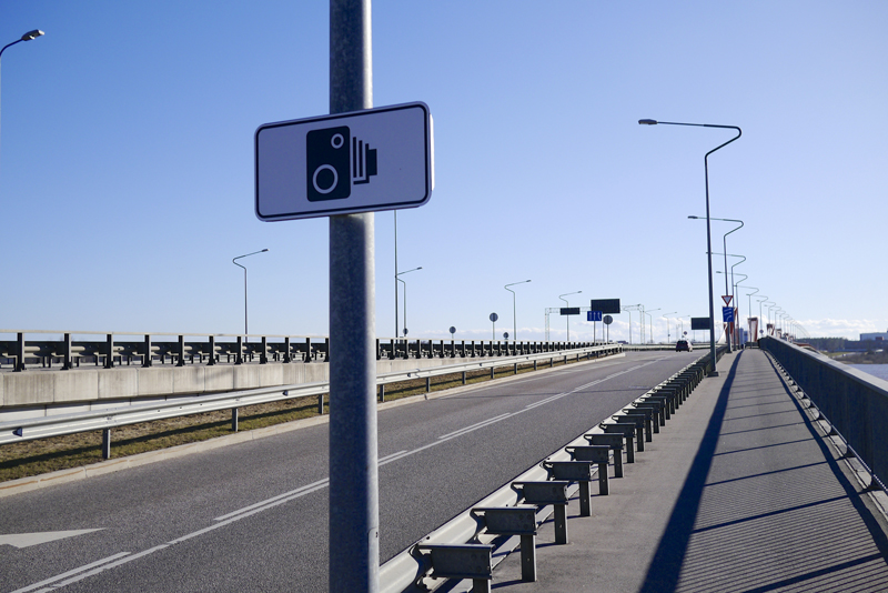 A speed camera sign on pole next to slip road to a busy bridge