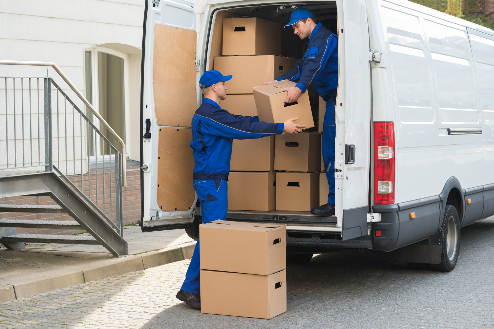 Two couriers unloading large boxes from the back of their van on a delivery