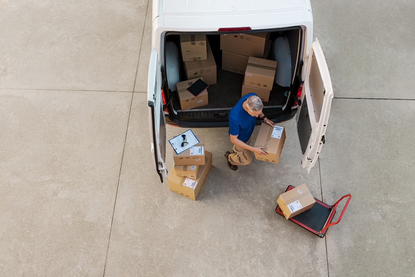 A delivery man taking a package from the back of a van