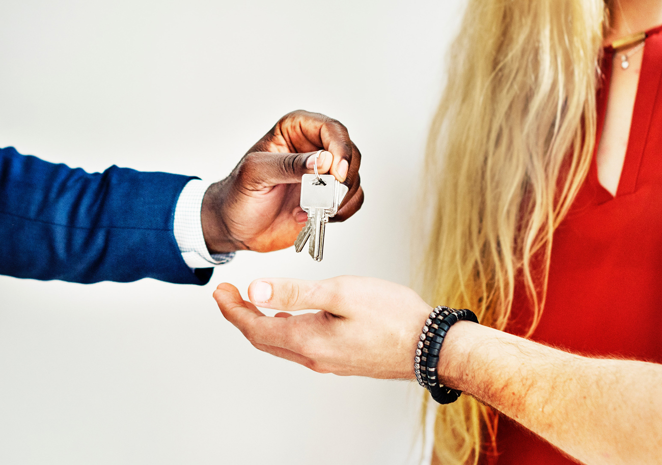 motor trade salesman handing over the keys to a car to a customer