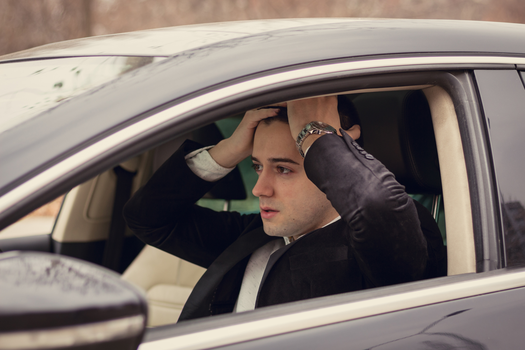 A man sitting in his car with his hands on his head after getting caught without car insurance